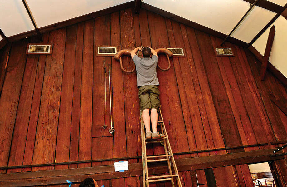 Hour photo / Erik Trautmann Travis Worrell of Simply Estated brings down a oxen yoke as the historic Red Barn Restaurant in Westport holds liquidation sale Saturday.