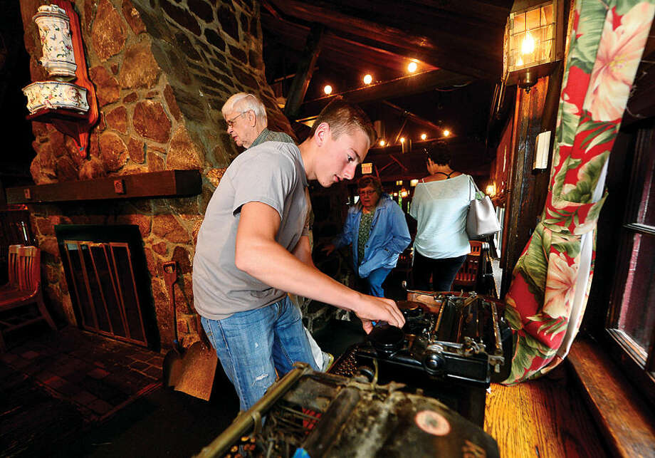 Hour photo / Erik Trautmann Michael McCarvill looks over an antique typewriter as the Red Barn Restaurant in Westport holds liquidation sale with Simply Estated Saturday.