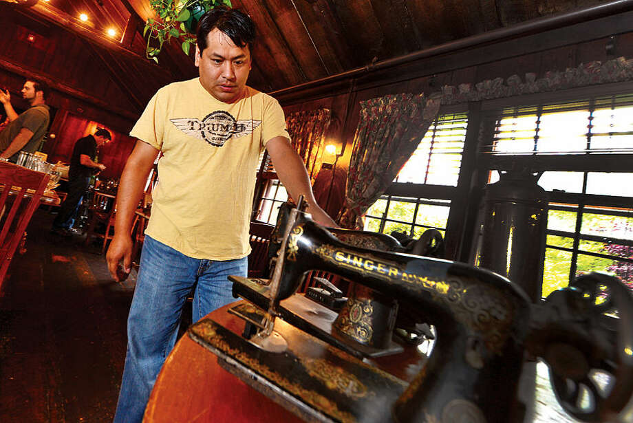Hour photo / Erik Trautmann Angel Vega tooks over an antiques sewing machine as the historic Red Barn Restaurant in Westport holds liquidation sale with Simply Estated Saturday.