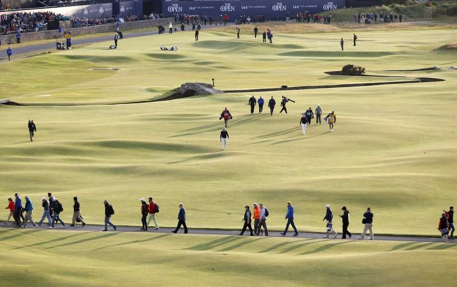 People make their way across the 18th hole during the second round of the British Open Golf Championship at the Old Course, St. Andrews, Scotland, Saturday, July 18, 2015. (AP Photo/Alastair Grant)