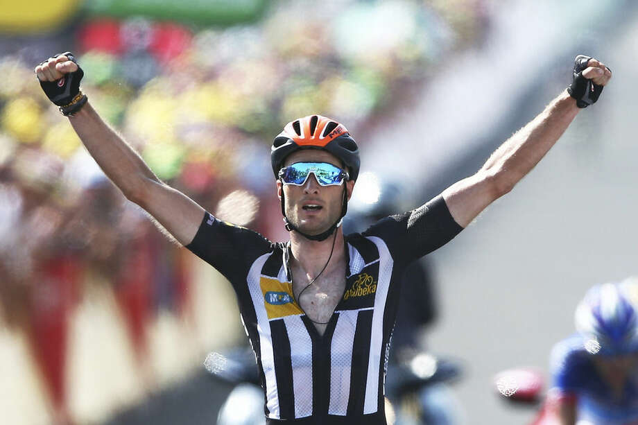 Britain's Stephen Cummings, wearing an orange helmet to mark Nelson Mandela's birthday, celebrates a she crosses the finish line to win the fourteenth stage of the Tour de France cycling race over 178.5 kilometers (110.9 miles) with start in Rodez and finish in Mende, France, Saturday, July 18, 2015. (AP Photo/Peter Dejong)