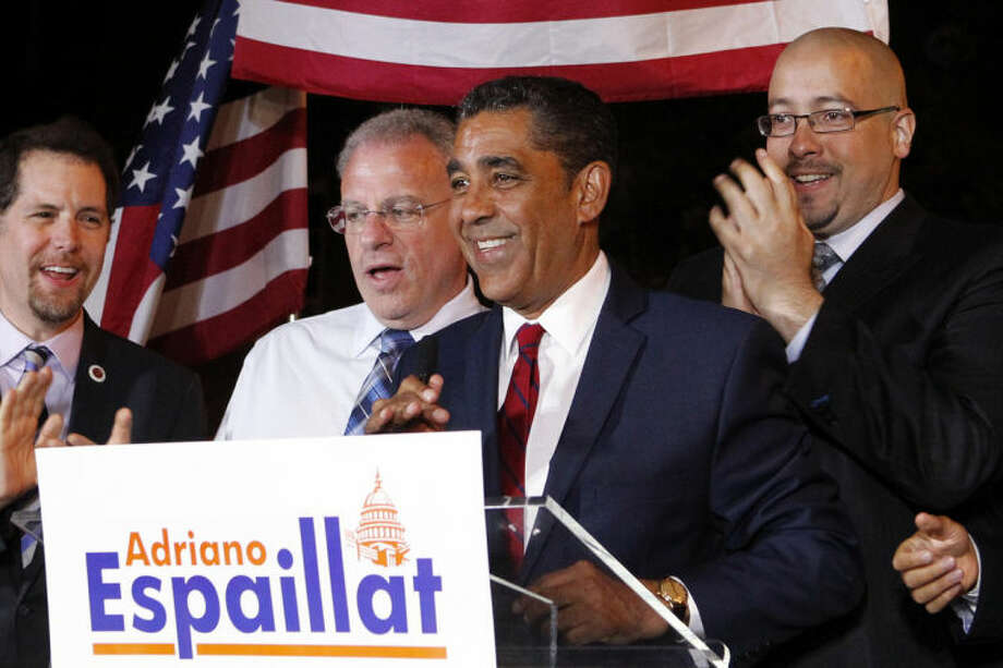 New York state senator Adriano Espaillat, center, declares his race with long-time Congressman Charles Rangel too close to call in the Democratic primary for the 13th Congressional District, Tuesday, June 24, 2014, in New York. Espaillat, a Dominican-born legislator who lost in the 2012 primary, is running against Rangel in the majority Hispanic district that includes Harlem. (AP Photo/Jason DeCrow)