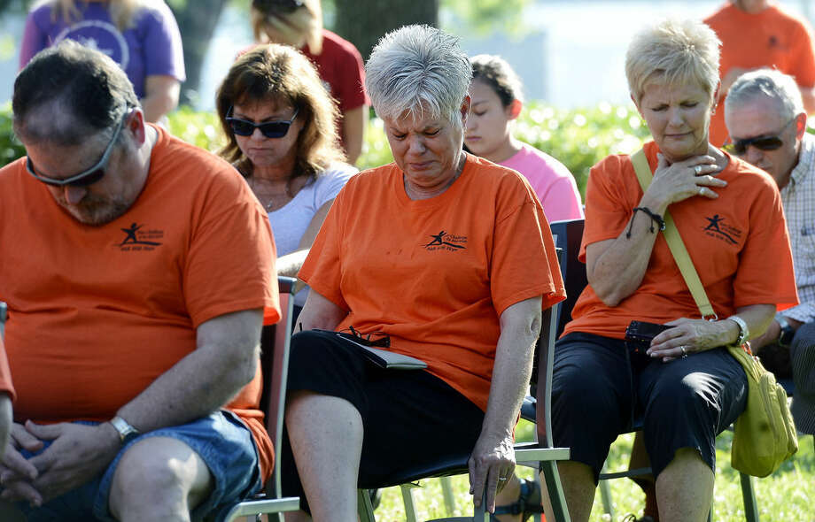 Teen Challenge member, Carol Parker, center, becomes emotional during a memorial service at River Park Saturday, July 18, 2015, in Chattanooga, Tenn., for the victims of the Tennessee shootings. The U.S. Navy says a sailor who was shot in the attack on a military facility in Chattanooga has died, raising the death toll to five people. (AP Photo/Mark Zaleski)