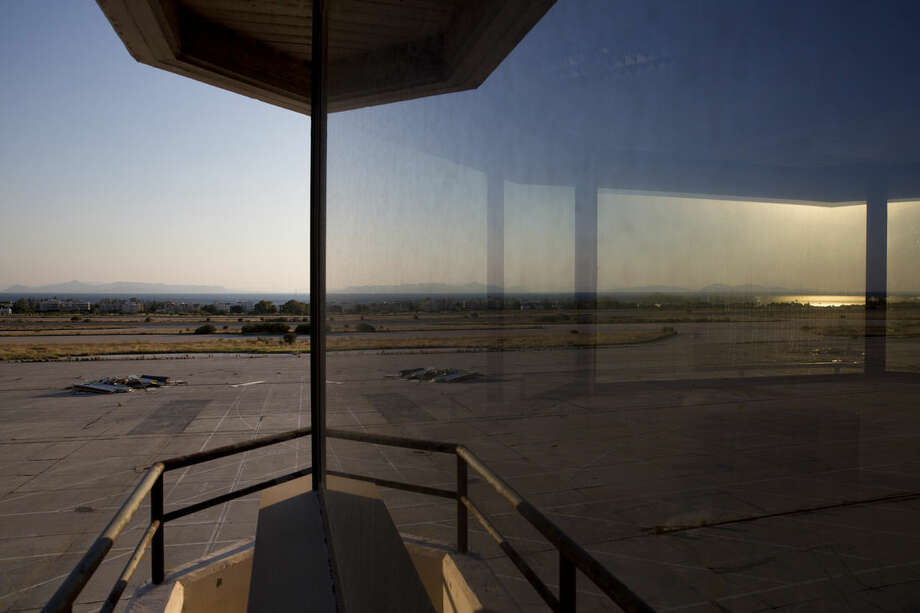 In this photo taken on Thursday, July 16, 2015,the runway of the abandoned old airport of Athens is reflected on the glass of the control tower. Now, in a bid to get a third European bailout, the ruling party has done an about face and is pledging to fast-track the waterfront project plus a host of other privatization efforts aimed at generating cash to help to reduce Greece's 320 billion euros national debt.(AP Photo/Petros Giannakouris)