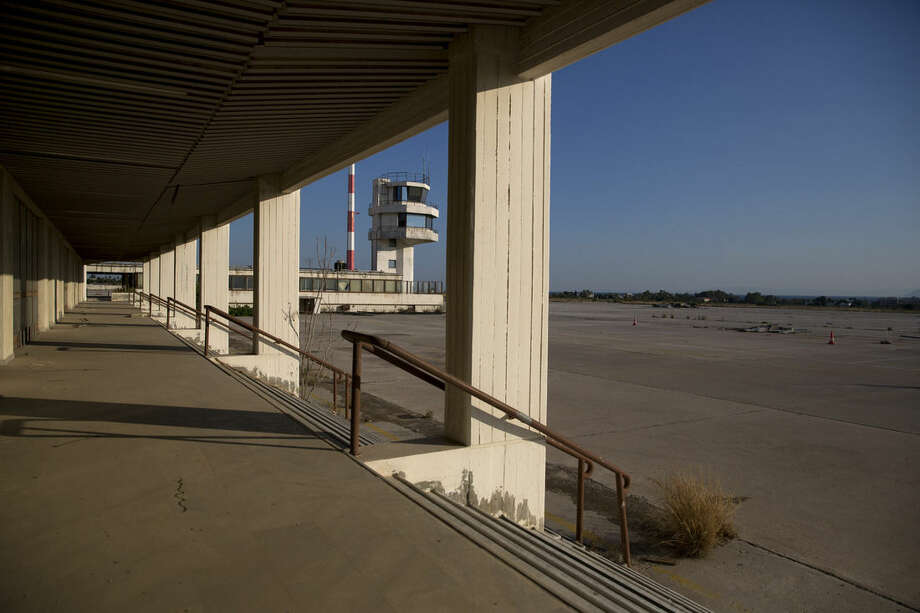 In this photo taken on Thursday, July 16, 2015, the runway of the abandoned old airport of Athens with the control tower on Thursday, July 16, 2015. Now, in a bid to get a third European bailout, the ruling party has done an about face and is pledging to fast-track the waterfront project plus a host of other privatization efforts aimed at generating cash to help to reduce Greece's 320 billion euros national debt. (AP Photo/Petros Giannakouris)