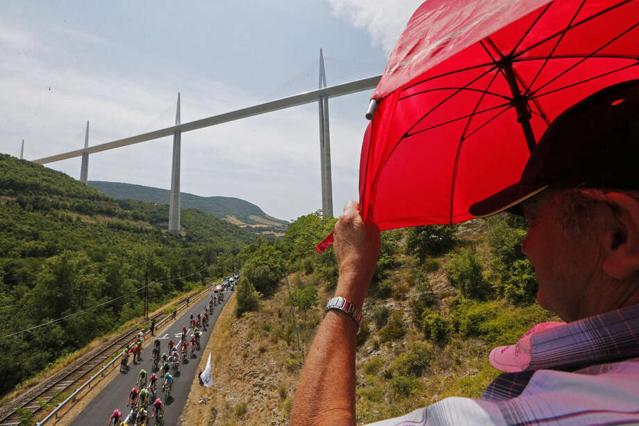 A spectator shields himself from the sun as the pack passes under the Millau viaduct, the tallest bridge in the world, cable-stayed with one mast's summit at 343 meters or 1,125 feet above the base of the structure, during the fourteenth stage of the Tour de France cycling race over 178.5 kilometers (110.9 miles) with start in Rodez and finish in Mende, France, Saturday, July 18, 2015. (AP Photo/Christophe Ena)