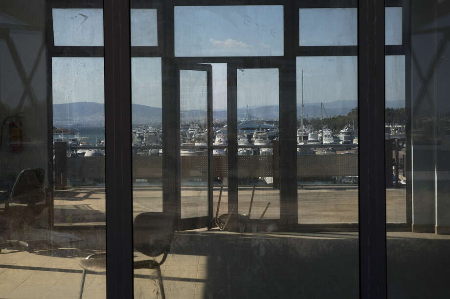In this photo taken on Thursday, July 16, 2015, yachts docked at the marina of Agios Kosmas are is seen through an abandoned building used for sailing events during Athens' 2004 Olympic games. Now, in a bid to get a third European bailout, the ruling party has done an about face and is pledging to fast-track the waterfront project plus a host of other privatization efforts aimed at generating cash to help to reduce Greece's 320 billion euros national debt.(AP Photo/Petros Giannakouris)
