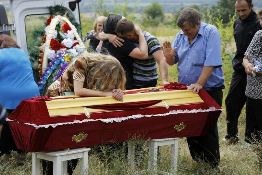 Relatives grieve at the coffin of pro-Russian fighter Dmitri Bystriukov, who was killed during a mortar attack, in the city of Krasnodon in Luhansk region, eastern Ukraine, Thursday, June 26, 2014. More than 300 people have been killed in eastern Ukraine in the past weeks as pro-Russian insurgents fought with government forces. Ukraine last Friday announced a unilateral cease-fire with the rebels. Some rebel groups said they would observe the cease-fire as well. (AP Photo/Dmitry Lovetsky)