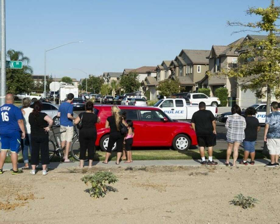 A small crowd gathers near a home where five people were found dead, Saturday, July 18, 2015, in Modesto, Calif. A Modesto police spokeswoman said officers responding to a request to conduct a welfare check discovered the bodies of three children and two adults Saturday afternoon. (John Westberg/The Modesto Bee via AP) NO SALES, MAGS OUT, TV OUT MANDATORY CREDIT