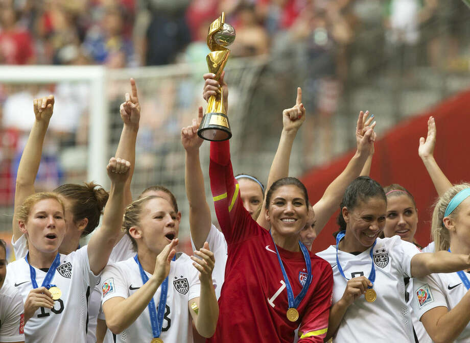 """FILE - In this July 5, 2015 file photo, United States goalkeeper Hope Solo hoists the trophy as she and her teammates celebrate defeating Japan to win the FIFA Women's World Cup soccer championship in Vancouver, British Columbia, Canada. The """"Kids' Choice Sports"""" awards show is adding a tribute to World Cup champion U.S. women's soccer team. Lloyd, Hope Solo and Alex Morgan are among the players set to appear, the Nickelodeon channel said Wednesday, July 15. (Darryl Dyck/The Canadian Press via AP) MANDATORY CREDIT"""