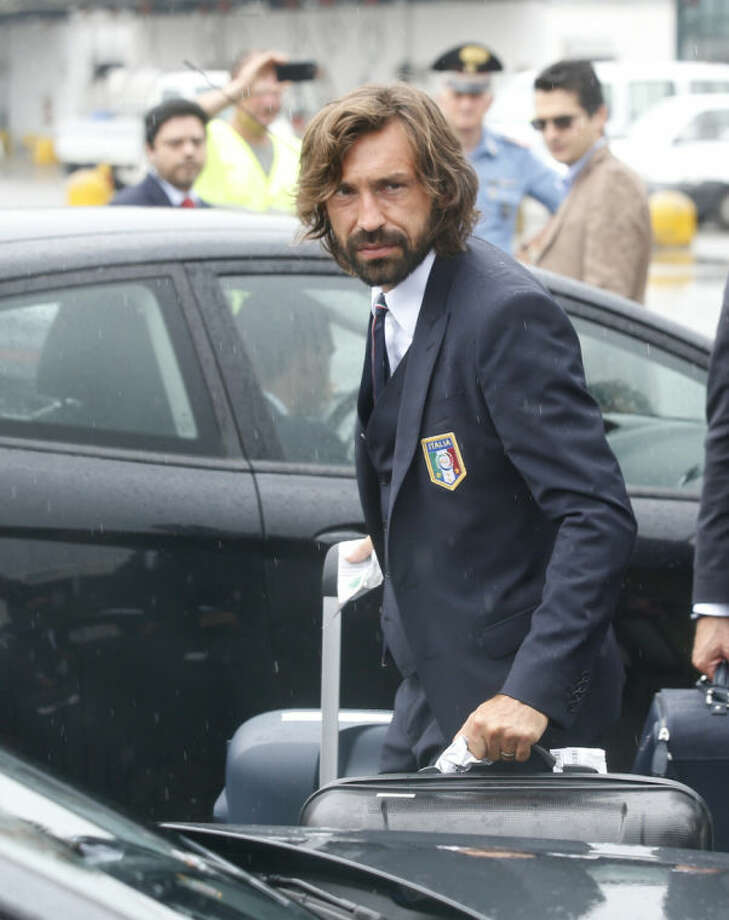 Italy soccer player Andrea Pirlo carries his luggage upon his arrival with his teammates at Malpensa airport after landing from Brazil, in Milan, Italy, Thursday, June 26, 2014. Italy was disqualified from the World Cup after loosing to Uruguay in their group stage round. (AP Photo/Luca Bruno)