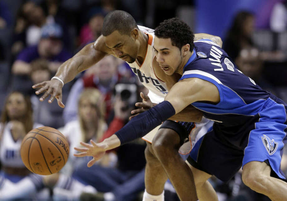 FILE - In this Feb. 11, 2014, file photo, Dallas Mavericks' Shane Larkin, right, tries to steal the ball from Charlotte Bobcats' Ramon Sessions during an NBA basketball game in Charlotte, N.C. Dallas and the New York Knicks have agreed to a trade that would bring center Tyson Chandler back to the Mavericks three years after he helped them win a championship only to leave right away in free agency. Two people with knowledge of the deal said Wednesday, June 25, 2014, the Mavericks would send guards Jose Calderon and Larkin and center Samuel Dalembert to the Knicks for Chandler and point guard Raymond Felton. The people spoke on condition of anonymity because the deal hasn't been announced. (AP Photo/Chuck Burton, File)
