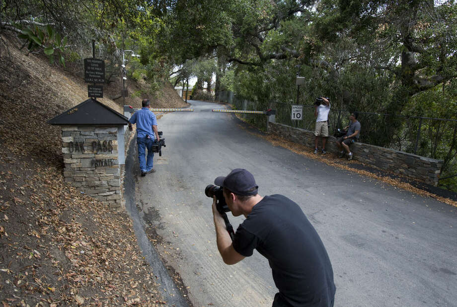 A photographer talks photos outside an entrance to to the home of actress Demi Moore, in Beverly Hills, Sunday, July 19, 2015. Coroner's officials say a 21-year-old man accidentally drowned in the backyard pool of a Los Angeles home owned by actress Demi Moore. (AP Photo/Ringo H.W. Chiu)