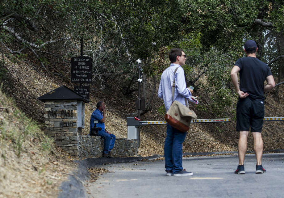 Members of the media wait outside of an entrance to to the home of actress Demi Moore, in Beverly Hills, Sunday, July 19, 2015. Coroner's officials say a 21-year-old man accidentally drowned in the backyard pool of a Los Angeles home owned by actress Demi Moore. (AP Photo/Ringo H.W. Chiu)