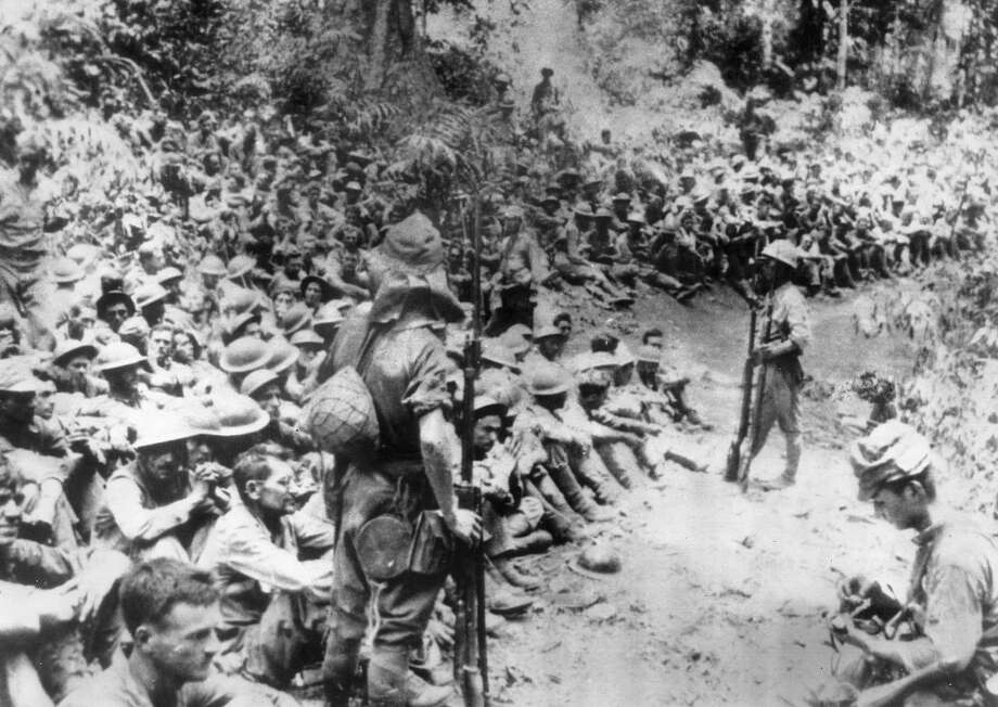 FILE - In this 1942 file photo provided by U.S. Marine Corps, Japanese soldiers stand guard over American war prisoners just before the start of the Bataan Death March following the Japanese occupation of the Philippines. A major Japanese corporation will offer a landmark apology on Sunday, July 19, 2015 for using U.S. prisoners of war for forced labor during World War II. A senior executive of Mitsubishi Materials Corp. will apologize to 94-year-old James Murphy and relatives of other former POWs who toiled at plants its predecessor company operated in Japan during the conflict. (U.S. Marine Corps via AP, File)