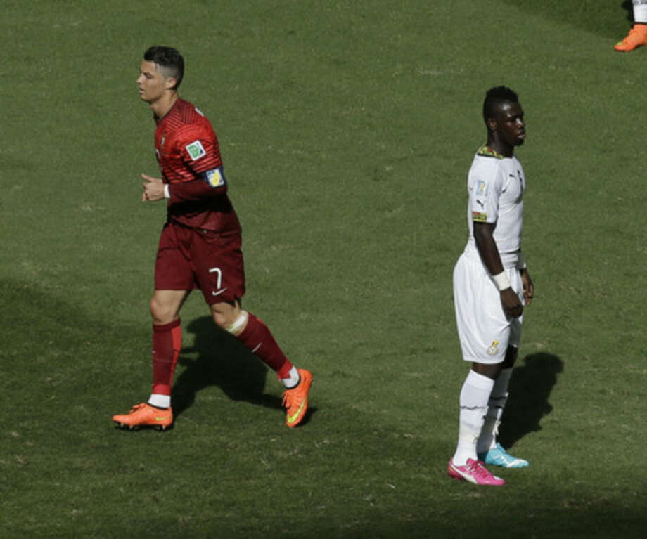 Portugal's Cristiano Ronaldo, left, runs past Ghana's Afriyie Acquah, right, after Ronaldo scored his side's 2nd goal during the group G World Cup soccer match between Portugal and Ghana at the Estadio Nacional in Brasilia, Brazil, Thursday, June 26, 2014. (AP Photo/Themba Hadebe)