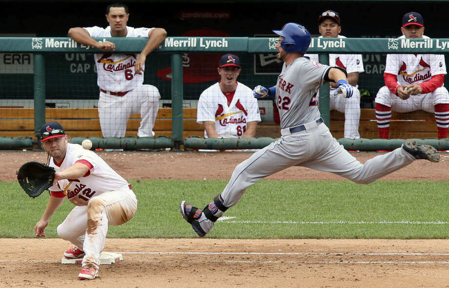 New York Mets' Kevin Plawecki (22) races the ball to first base as St. Louis Cardinals first baseman Mark Reynolds receives the throw during the 11th inning of a baseball game, Sunday, July 19, 2015 in St. Louis. (Chris Lee/St. Louis Post-Dispatch via AP) EDWARDSVILLE INTELLIGENCER OUT; THE ALTON TELEGRAPH OUT; MANDATORY CREDIT
