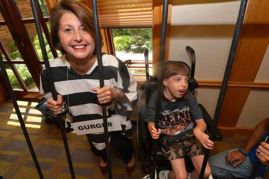 Hour Photo/Alex von Kleydorff Susan Valente with Ritz Realty Corp is behind bars with Goodwill Ambassador Dakota Fortier at the Dolce Center Lock Up for the 2014 MDA Lock Up to raise money for Muscular Dystrophy Association