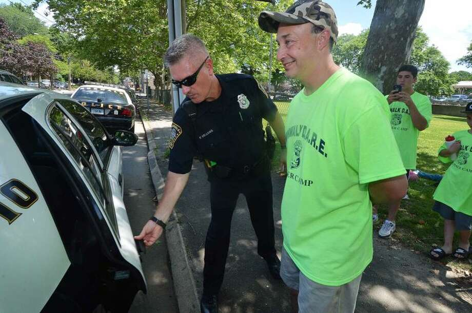 Hour Photo/Alex von Kleydorff Norwalk Police Officer Chris Holms is handcuffed and taken into custody by fellow officer Fred Kellogg during the 2014 MDA Lock Up to raise money for Muscular Dystrophy Association