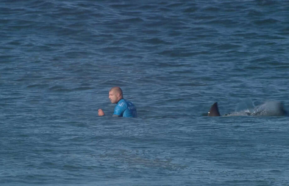 In this screen shot taken from video made available by the World Surf League, Australian surfer Mick Flanning is pursued by a shark, in Jeffrey's Bay, South Africa, Sunday, July 19, 2015. Knocked off his board by an attacking shark, a surfer punched the creature during the televised finals of a world surfing competition in South Africa before escaping. Fanning was attacked by a shark on Sunday during the JBay Open but escaped without injuries. (W orld Surf League via AP) MANDATORY CREDIT FOR ALL ONLINE USE PLEASE INCLUDE A LINK TO WORLDSURFLEAGUE.COM.
