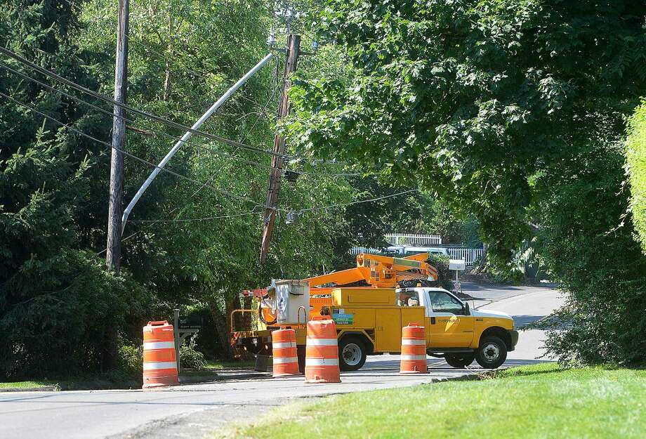 Hour Photo/Alex von Kleydorff A crew from Eversource Energy at the scene of a snapped utility pole on Bluff Ave in Rowayton on Monday morning. The pole was broken by a commercial refuse truck which closed Bluff ave to traffic