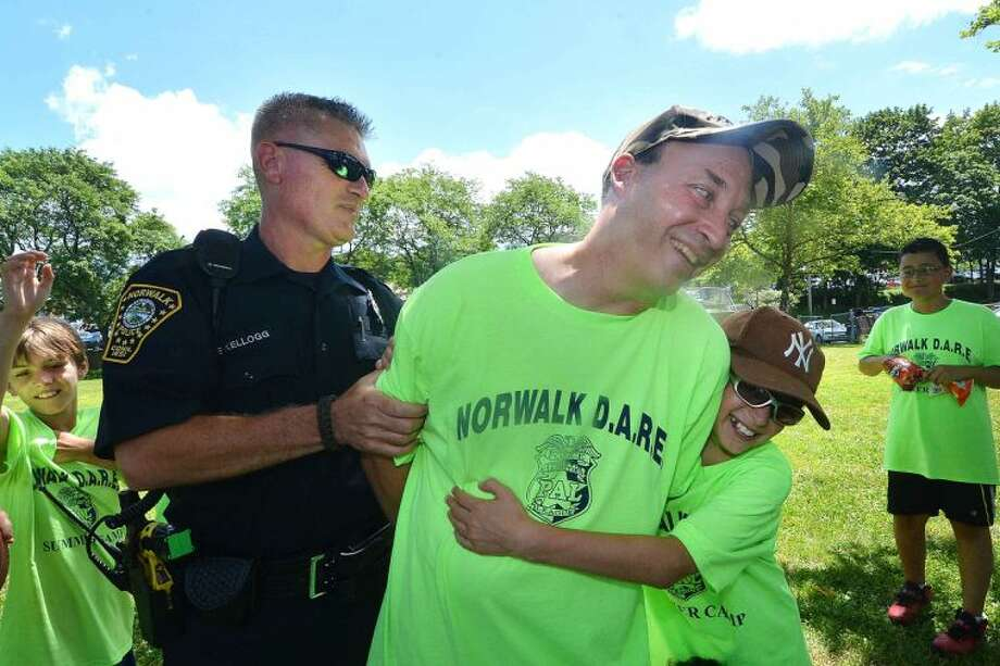 Hour Photo/Alex von Kleydorff Norwalk Police Officer Chris Holms is handcuffed as his DARE Camp kids try to resist and taken into custody by fellow officer Fred Kellogg during the 2014 MDA Lock Up to raise money for Muscular Dystrophy Association