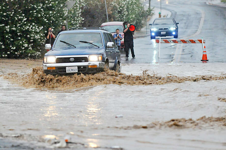 A vehicle drives through a flooded section of the road that was closed off on Pebble Beach Drive in Victorville, Calif, Sunday, July 19, 2015. A summer storm delivered rain, thunder and lightning to central and southern California on Saturday, leading to beach closures, flash floods and outages that left tens of thousands of people without power. (David Pardo/The Victor Valley Daily Press via AP) MANDATORY CREDIT