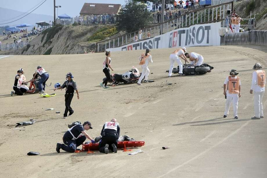 In this Sunday, July 19, 2015, photo, medical and track personnel attend to downed riders after a chain reaction crash on the first lap of a World Superbike race at Mazda Raceway at Laguna Seca in Monterey, Calif. Two Spanish racers were killed in the crash. Race organizers MotoAmerica identified the dead as 35-year-old Bernat Martinez and 27-year-old Daniel Rivas Fernandez. Both were taken to hospitals, where they later died. (Nic Coury/Monterey County Weekly via AP) MANDATORY CREDIT FOR PAPER AND PHOTOGRAPHER. MONTEREY HERALD OUT , SALINAS CALIFORNIAN OUT , SANTA CRUZ SENTINEL OUT , SAN JOSE MERCURY OUT , LOCAL TV OUT