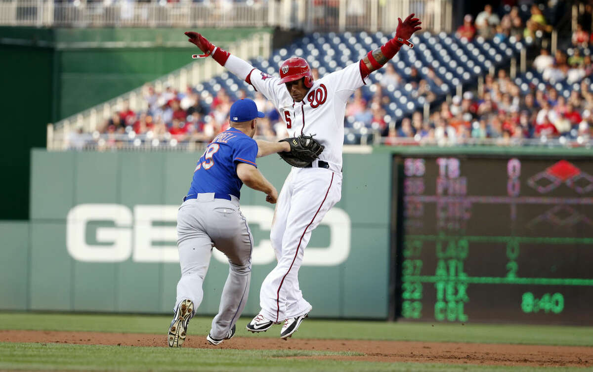 Washington Nationals' Yunel Escobar (5) is tagged out on a run down between first and second bases by New York Mets first baseman Eric Campbell during the first inning of a baseball game at Nationals Park, Monday, July 20, 2015, in Washington. (AP Photo/Alex Brandon)