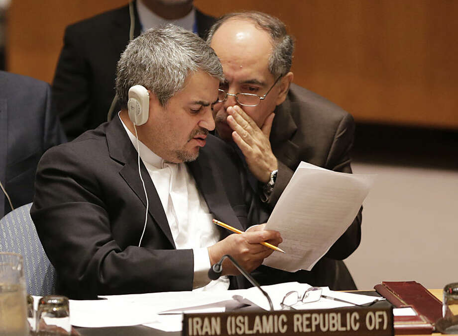 Iran's United Nations Ambassador Gholamali Khoshroo, left, listens to a member of his delegation following a vote on a resolution approving Iran's nuclear deal at United Nations headquarters, Monday, July 20, 2015. (AP Photo/Mark Lennihan)