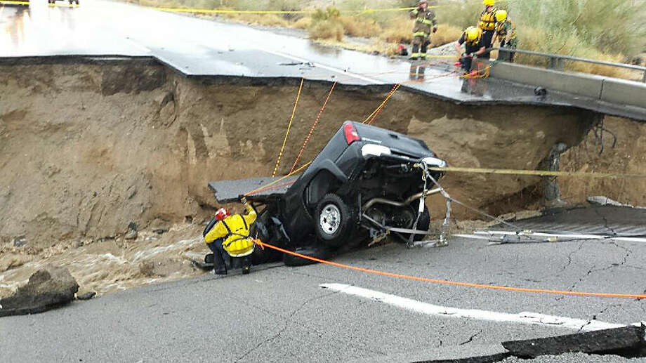 In this photo provided by the CAL FIRE/Riverside County Fire Department, emergency crews respond after a pickup truck crashed into the collapse of an elevated section of Interstate 10, Sunday, July 19, 2015, in Desert Center, Calif. The bridge, which carries the eastbound interstate about 15 feet above a normally dry wash, snapped and ended up in the flooding water below, the California Highway Patrol said, blocking all traffic headed toward Arizona. (Chief Geoff Pemberton/CAL FIRE/Riverside County Fire via AP) MANDATORY CREDIT