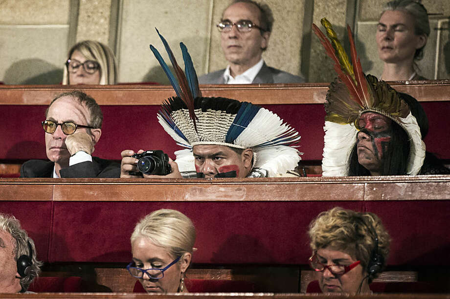 Delegates, some in traditional dress, attend the opening of the Consciousness Summit in Paris, France, Tuesday, July 21, 2015. French president Francois Hollande called for an ambitious accord on climate ahead of a UN conference in Paris to address the threat of global warning. (Etienne Laurent/Pool Photo via AP)