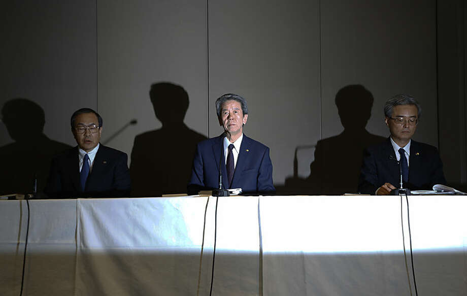 """Toshiba Corp. CEO Hisao Tanaka, center, speaks with chairman Tadashi Muromachi, left, and executive director Keizo Maeda, right, during a press conference to announce his resignation at the company's headquarters in Tokyo, Tuesday, July 21, 2015. Tanaka stepped down Tuesday to take responsibility for doctored books that inflated profits at the Japanese technology manufacturer by 151.8 billion yen ($1.2 billion). Toshiba acknowledged a systematic cover-up, which began in 2008, as various parts of its sprawling business including computer chips and personal computers were struggling financially, but top managers set unrealistic earnings targets under the banner of """"challenge."""" (AP Photo/Shizuo Kambayashi)"""