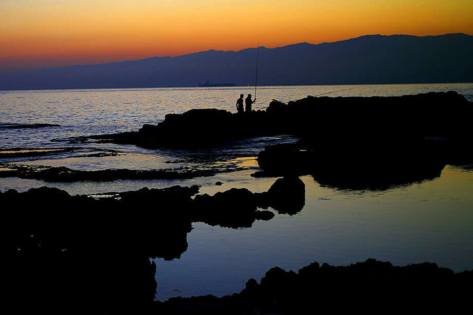 Lebanese anglers cast fishing poles from a rocky coastal area along the Beirut coastline as the sun rises over the Mediterranean Sea in Lebanon, Tuesday, July 21, 2015. (AP Photo/Hassan Ammar)