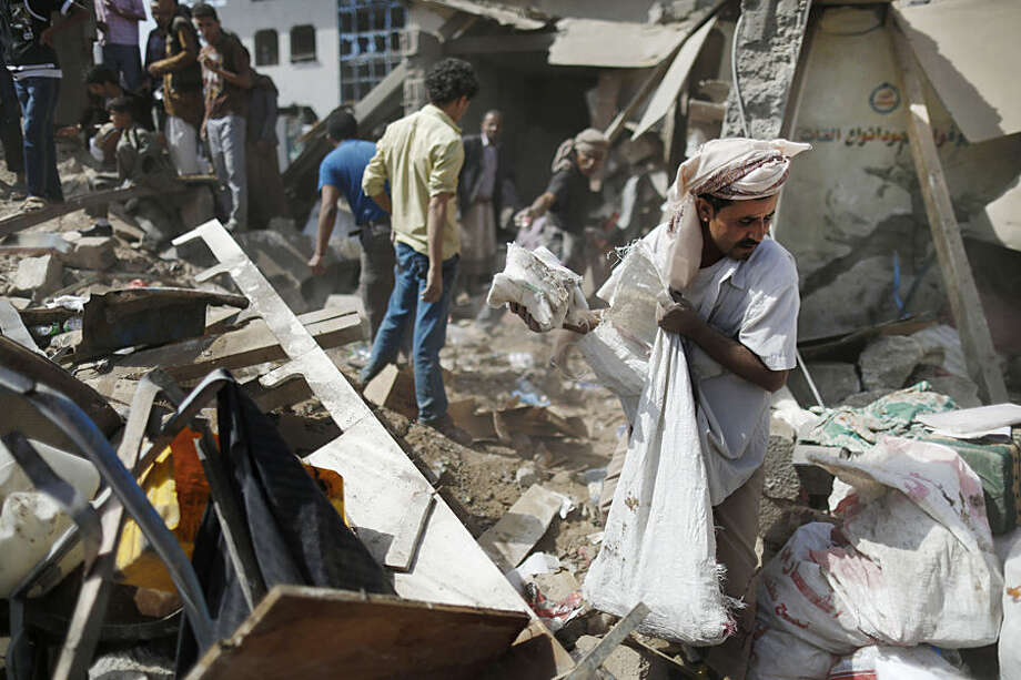 """A vendor salvages goods from the rubble of his shop destroyed by a Saudi-led airstrike at a market in Sanaa, Yemen, Monday, July 20, 2015. The death toll in Yemen from the Shiite rebel shelling of a town near the southern port city of Aden rose on Monday to nearly 100, the head of an international aid group said, describing it as """"the worst day"""" for the city and its surroundings in over three months of fighting. (AP Photo/Hani Mohammed)"""