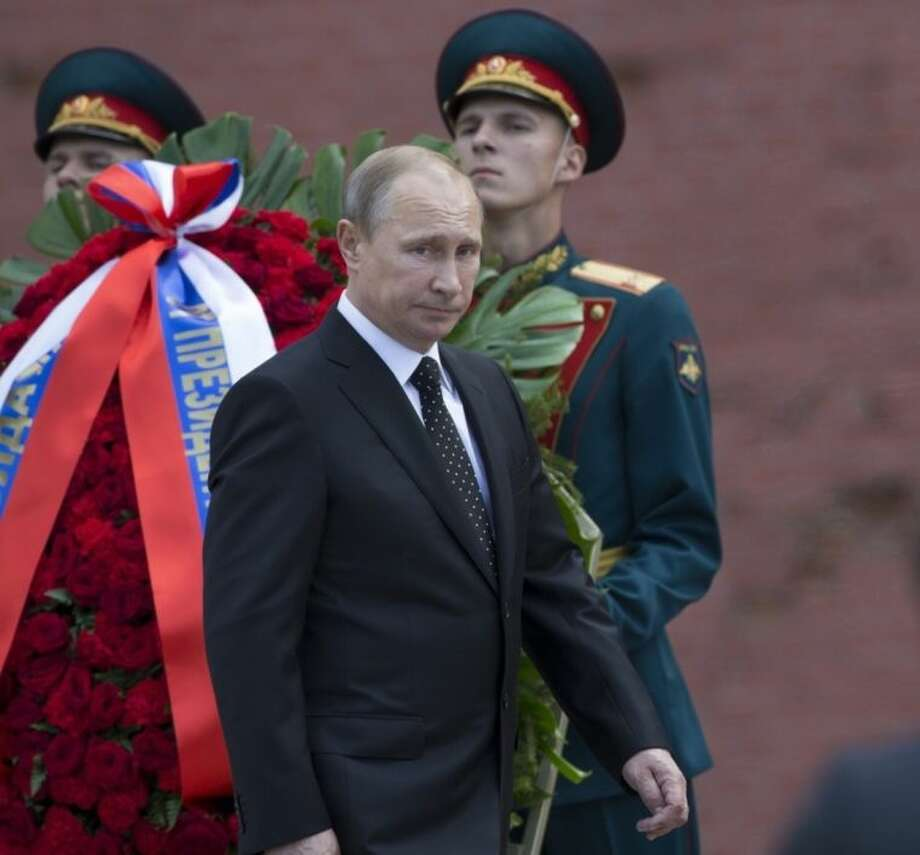 Russian President Vladimir Putin takes part in a wreath laying ceremony at the Tomb of the Unknown Soldier outside Moscow's Kremlin Wall, in Moscow, Russia, Sunday, June 22, 2014 to mark the 73rd anniversary of the Nazi invasion of the Soviet Union. (AP Photo/Alexander Zemlianichenko)