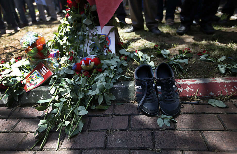 A pair of shoes belonging to a victim are seen next to flowers, laid down by mourners at the site of Monday's explosion in the Turkish town of Suruc near the Syrian border, Tuesday, July 21, 2015. Authorities suspected the Islamic State group was behind an apparent suicide bombing Monday in Suruc in southeastern Turkey that killed 31 people and wounded nearly 100 — a development that could represent a major expansion by the extremists at a time when the government is stepping up efforts against them. (AP Photo/Emrah Gurel)