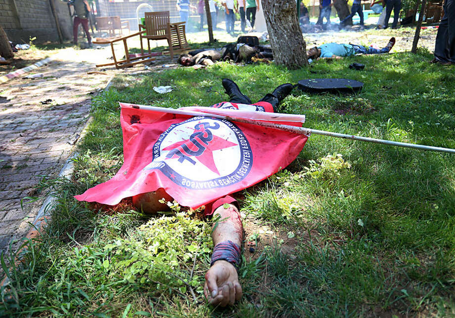 Bodies lie on the ground with one being covered with a Federation of the Socialist Youth Associations flag, after an explosion, in the southeastern Turkish city of Suruc near the Syrian border, Turkey, Monday, July 20, 2015. An explosion Monday killed at least 10 people and injured scores of others in the southeastern Turkish city of Suruc near the Syrian border, state-run Turkish news agencies reported. The private Turkish DHA news agency said at least 50 people had been hospitalized in the midday explosion. There was no immediate claim of responsibility for the blast. (AP Photo/Ozcan Soysal ) TURKEY OUT