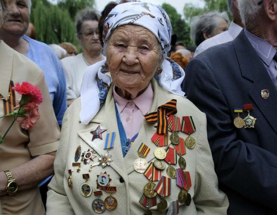 WWII veterans attend the ceremony of laying flowers to the Eternal flame, dedicated to the Day of Memory and grief, surrounding the events of World War II, in Simferopol, Crimea, Sunday, June 22, 2014. (AP Photo/Alexander Polegenko)