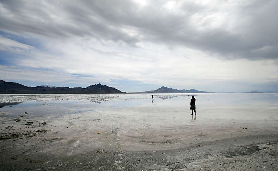 This Saturday, July 18, 2015, photo, shows visitors walking on the Bonneville Salt Flats, in Utah. The Speed Week races that draw hundreds of racing teams from around the world to Utah's famous salt flats have been canceled for the second consecutive year because of wet conditions. The event organizers announced the cancellation Monday, July 20, of an event that was scheduled to start Aug. 8. (AP Photo/Rick Bowmer)