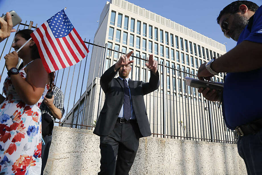 An employee of the United States Embassy Havana asks pedestrians to move back and away from the embassy gates, Monday, July 20, 2015. The U.S. Interests Section in Havana plans to announce its upgrade to embassy status in a written statement on Monday, but the Stars and Stripes will not fly at the mission until Secretary of State John Kerry visits in August for a ceremonial flag-raising. (AP Photo/Desmond Boylan)
