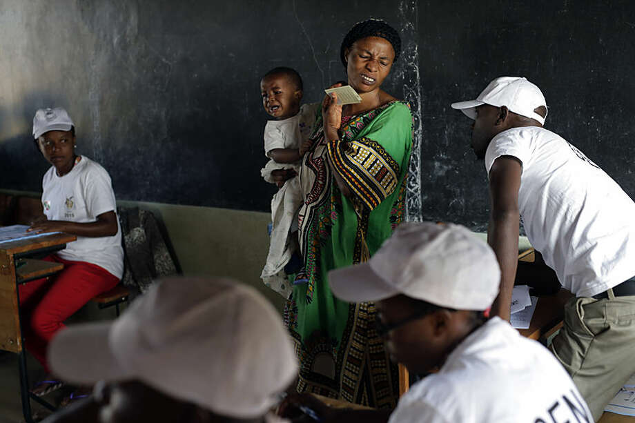 A woman carrying her baby grimaces after being turned away for not being in the proper polling station in the presidential elections in Bujumbura, Burundi, Tuesday July 21, 2015. A low turnout was experienced in several polling stations in the Burundi's capital at the start of voting in the country's presidential election following a night of explosions and gunfire in at least two opposition strongholds that oppose President Pierre Nkurunziza's candidacy for a third term in office. (AP Photo/Jerome Delay)