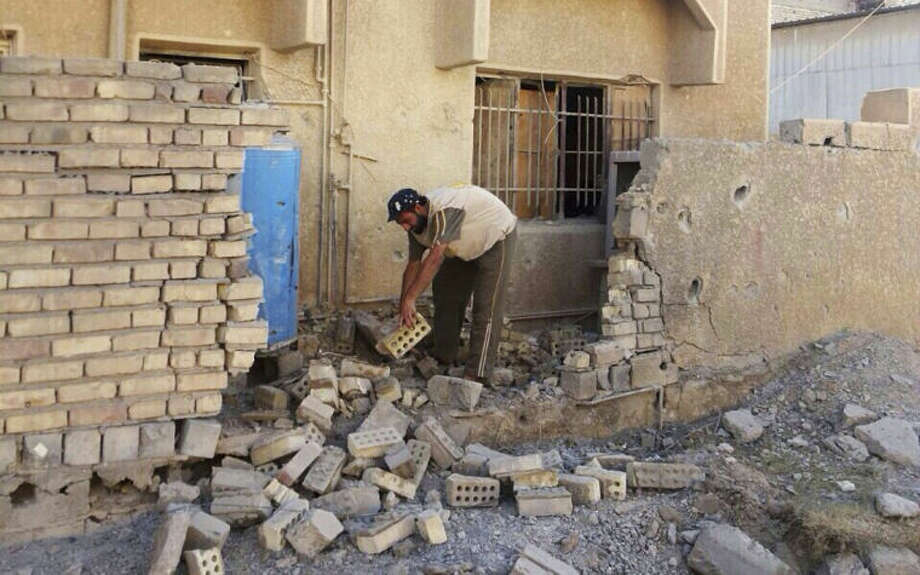 Abu Rasool al-Kubaisi clears debris at his home after a bombing in Fallujah, 40 miles (65 kilometers) west of Baghdad, Iraq, Sunday, June 22, 2014. Sunni militants have seized another town in Iraq's western Anbar province, the fourth to fall in two days, officials said Sunday, in what is shaping up to be a major offensive in one of Iraq's most restive regions. (AP Photo)
