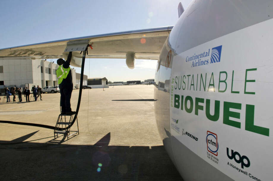 FILE - In this Jan. 7, 2009 file photo, Monte Hawkins prepares to remove the fuel line attached to a Continental Airlines jet for the first biofuel-powered demonstration flight of a U.S. commercial airliner, at Bush Intercontinental Airport in Houston. Many in the industry believe that without a replacement for jet fuel, growth in air travel could be threatened by forthcoming rules that limit global aircraft emissions. (AP Photo/David J. Phillip, File)