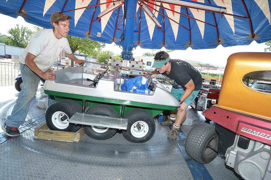 Hour Photo/Alex von Kleydorff Rainbow Amusements' Bryan Williams and Sean Ermark get one of the kiddie cars on track on the umbrella ride, setting up for this weekends St Ann Feast at the Saint Ann Club on Hendricks Ave.