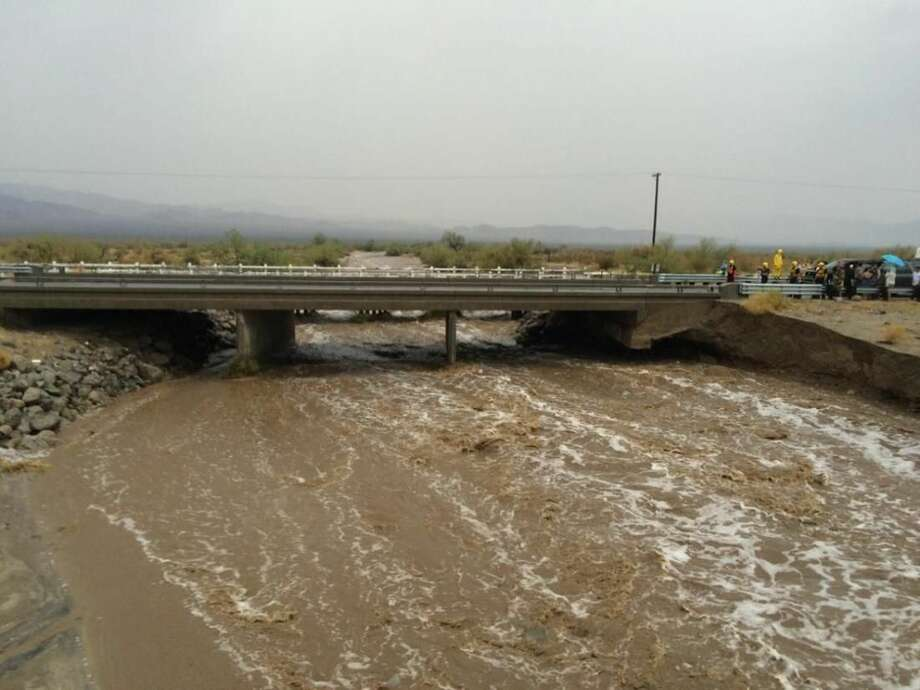 In this photo provided by the CAL FIRE/Riverside County Fire Department, waters rush under an the elevated portion westbound Interstate 10 as emergency crews respond to the collapse of the eastbound section, Sunday, July 19, 2015, in Desert Center, Calif. The bridge, which carries the eastbound interstate about 15 feet above a normally dry wash, snapped and ended up in the flooding water below, the California Highway Patrol said, blocking all traffic headed toward Arizona. (Chief Geoff Pemberton/CAL FIRE/Riverside County Fire via AP) MANDATORY CREDIT