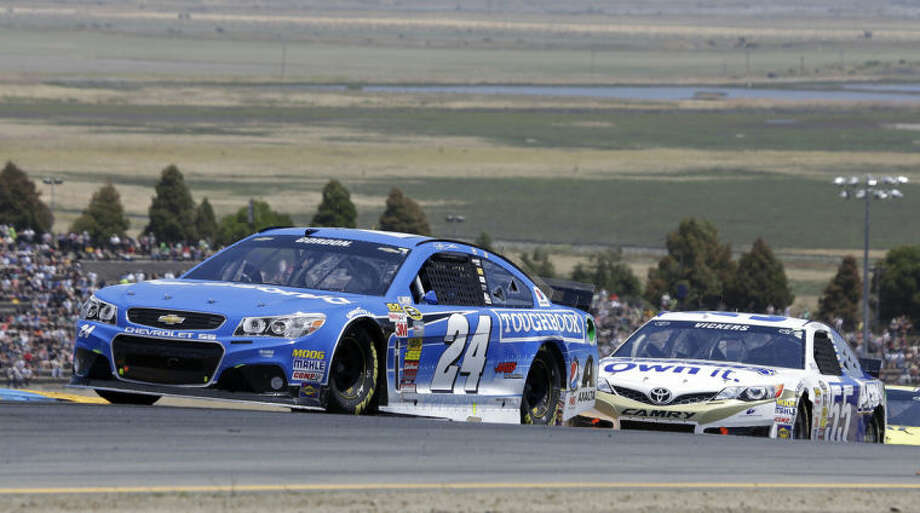 Jeff Gordon leads Brian Vickers during the NASCAR Sprint Cup Series auto race Sunday, June 22, 2014, in Sonoma, Calif. (AP Photo/Eric Risberg)