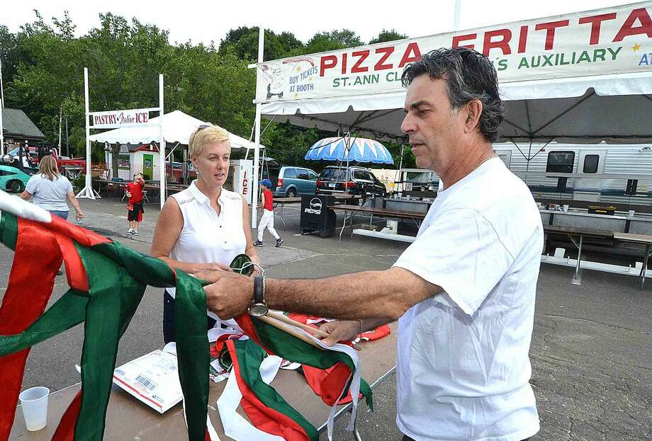 Hour Photo/Alex von Kleydorff Jen Veno and Sal Fratino work on setting up italian flags along the midway for the St Ann feast this weekend
