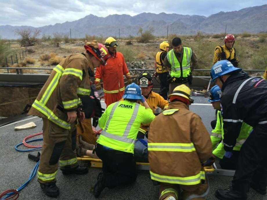 In this photo provided by the CAL FIRE/Riverside County Fire Department, emergency crews help a driver after their pickup truck crashed into the collapse of an elevated section of Interstate 10, Sunday, July 19, 2015, in Desert Center, Calif. The bridge, which carries the eastbound interstate about 15 feet above a normally dry wash, snapped and ended up in the flooding water below, the California Highway Patrol said, blocking all traffic headed toward Arizona. (Chief Geoff Pemberton/CAL FIRE/Riverside County Fire via AP) MANDATORY CREDIT