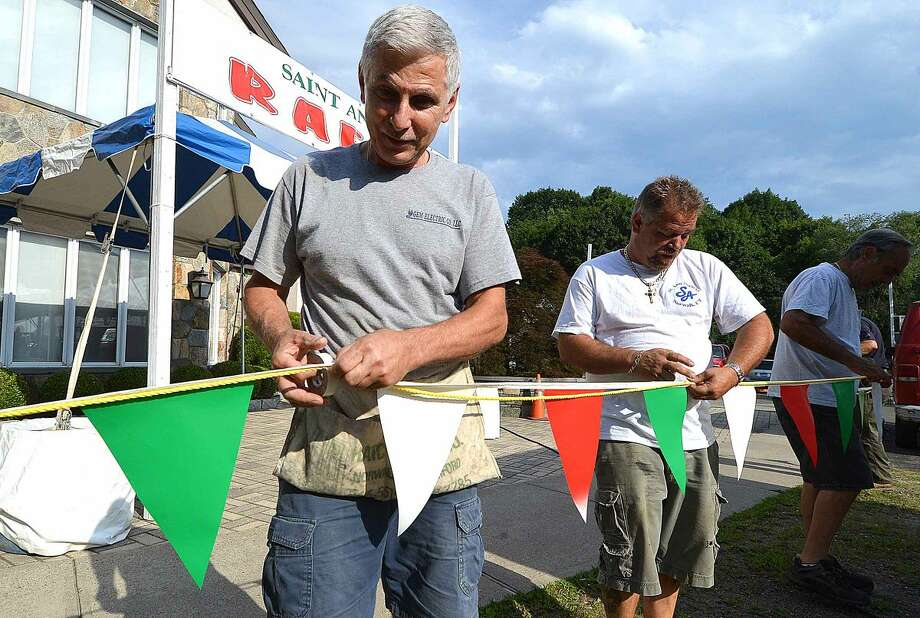Hour Photo/Alex von Kleydorff Emilio Granata tapes up flags for the raffle booth for the St Ann feast this weekend